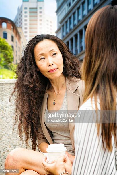 Professional mature Japanese woman listening to younger colleague