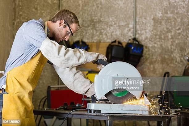 Professional metalworker using metal saw in workshop or studio