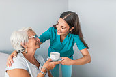 Professional nurse and smiling senior woman laughing while sitting in common room and drinking tea