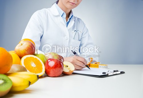 Professional nutritionist writing medical records : Stock Photo
