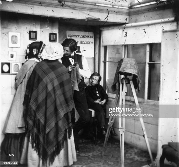 A professional photographer consults with clients in his studio circa 1860