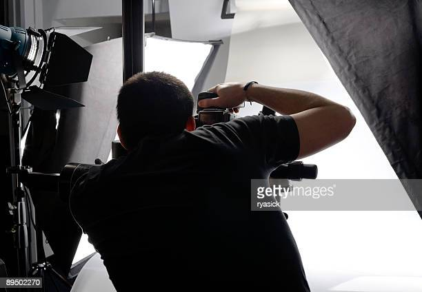 Professional Photographer From Behind Looking Through Viewfinder In Studio