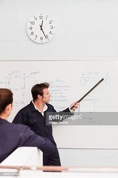 Professional plumber teaching apprentice in front of whiteboard