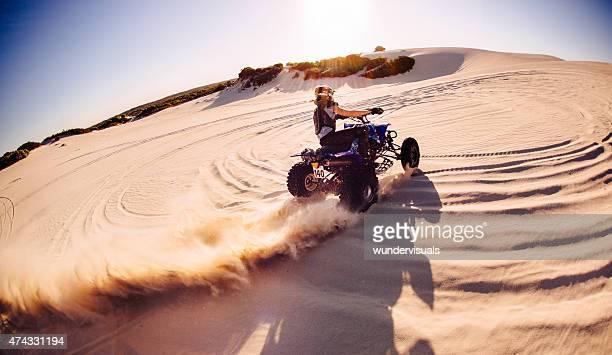 Professional quad biker kicking up sand on a dune