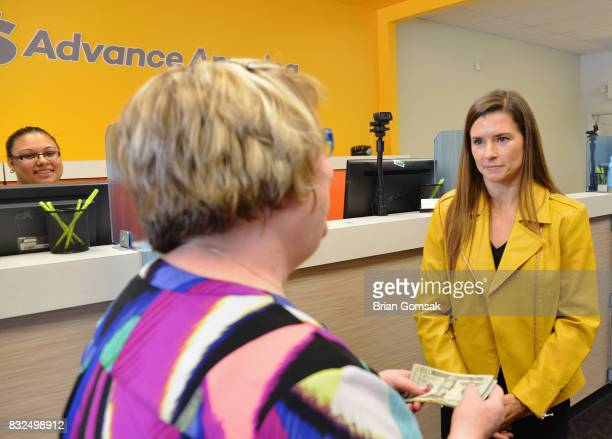 Professional Race Car Driver and Advance America Brand Ambassador Danica Patrick surprises customer Janice Walker by paying her bill in celebration...