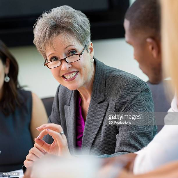 Professional senior executive woman talking in meeting with colleagues