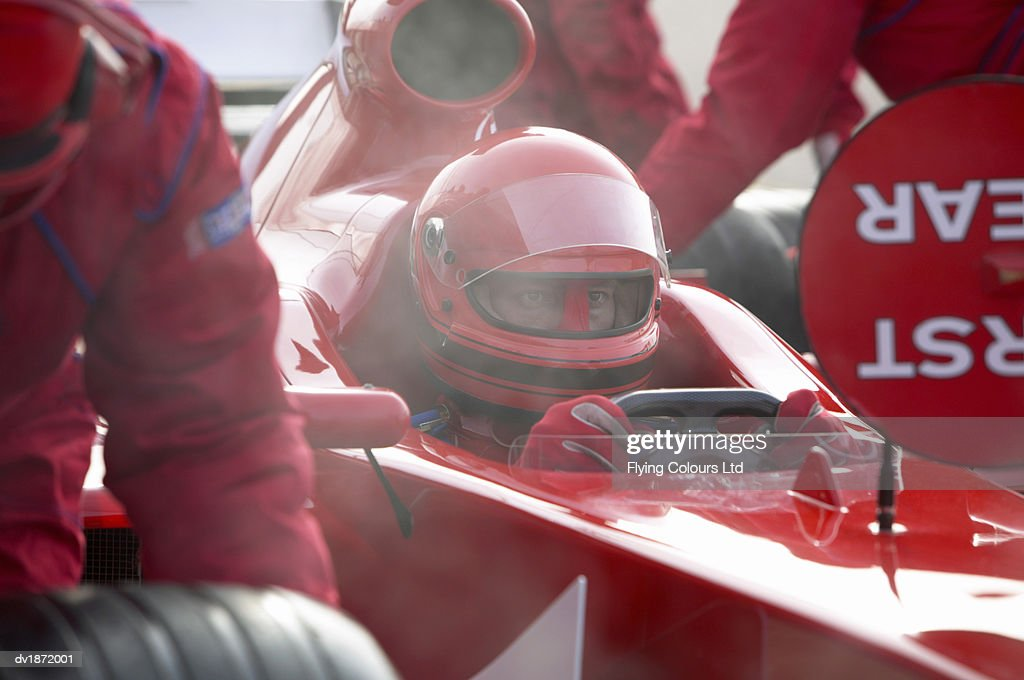 Professional Sports Driver Sitting in a Formula One Racing Car as Mechanics Perform a Pit Stop : Stock Photo