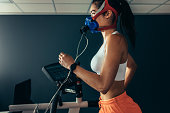 Side view of professional sportswoman with mask running on treadmill in gym. Female athlete in sports science lab measuring her performance and oxygen consumption.