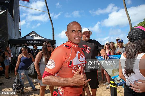 Professional surfer Kelly Slater poses for a picture and flashes a 'shaka' sign at Waimea Bay on February 25 2016 in Waimea Hawaii