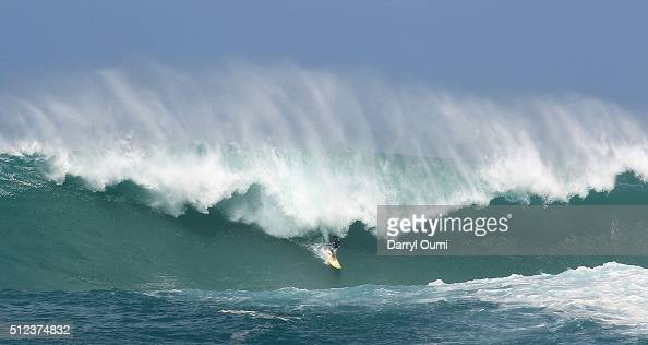 Professional surfer Mason Ho rides a wave at The Quiksilver in Memory of Eddie Aikau at Waimea Bay on February 25 2016 in Waimea Hawaii