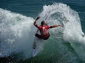 Professional surfer Mitch Crews of Australia does a cutback as he competes during his round two men's heat of the US Open of Surfing in Huntington...