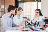 Working atmosphere. Selective focus on concentrated elegant engineer woman is holding robot with slight smile. She is demonstrating it to her colleagues