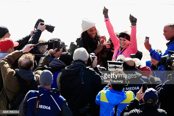 Professional tennis player Caroline Wozniacki of Denmark celebrates alongside Serena Williams of the United States as the media looks on after...