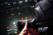 Professional video camera man film concert on stage.Big pro 4k video cam shoots live broadcast footage for television.TV camera operator shooting videos on concert stage