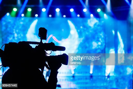 Professional Video camera operator working with his equipment, blue background : Foto stock