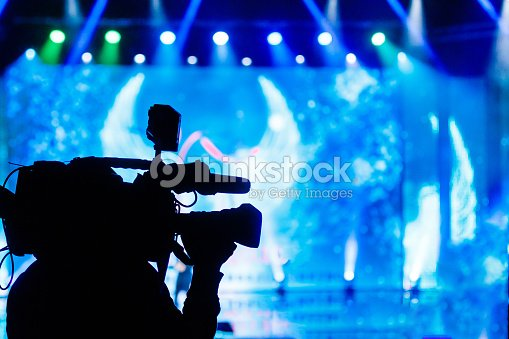 Professional Video camera operator working with his equipment, blue background : Stock Photo