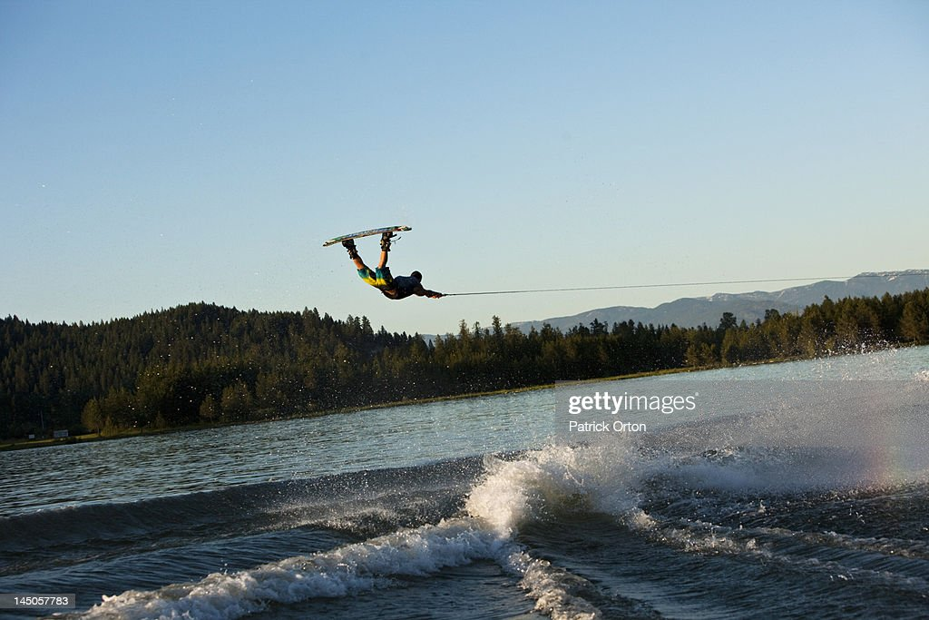 A professional wakeboarder jumps the wake on a lake in Idaho. : Stock Photo