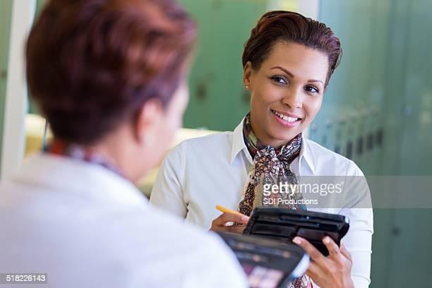 Professional woman applying makeup in gym locker room