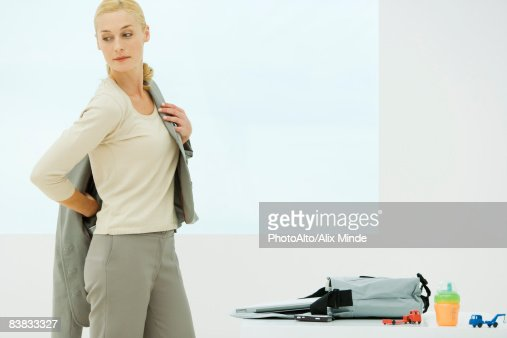 Professional woman dressing, looking over shoulder, sippy cup and toys next to bag
