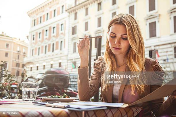 Professional woman filling documents at the restaurant