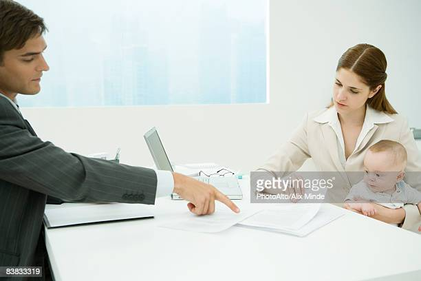 Professional woman in office, holding baby on lap, discussing documents with male colleague