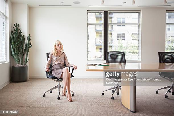 Professional woman sitting in a meeting room alone
