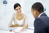 Professional woman sitting with client at desk, discussing brochure