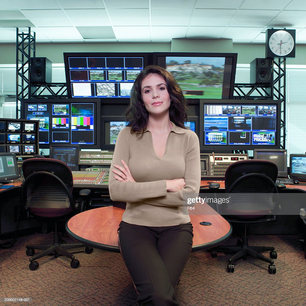 Professional woman standing in television studio control room