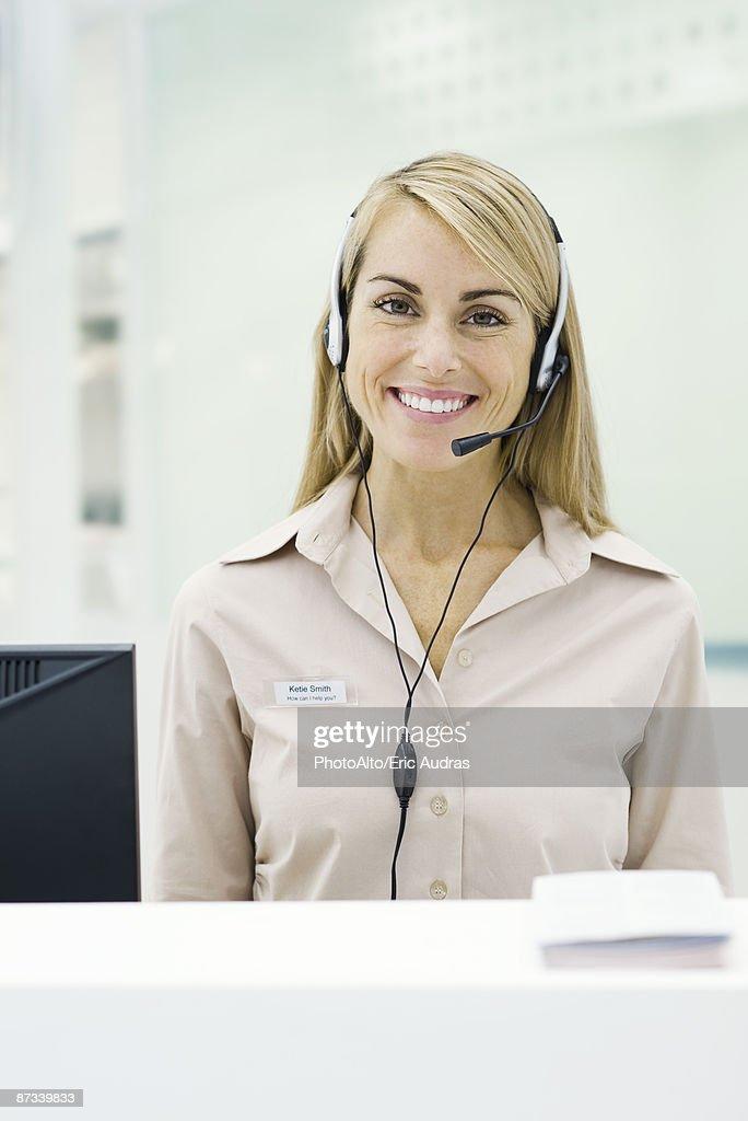 Professional woman wearing headset, smiling at camera
