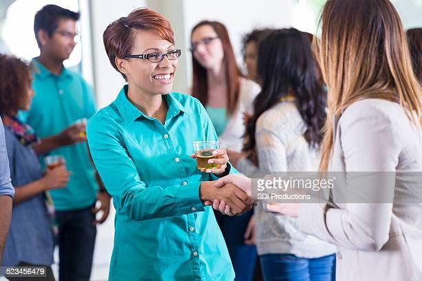 Professionelle Frauen beim Händeschütteln bei Mischpult oder party