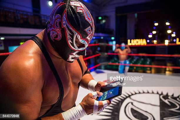 Professional wrestler and actor Silver King checks his phone during a photo call at York Hall in Bethnal Green on July 1 2016 in London England A...