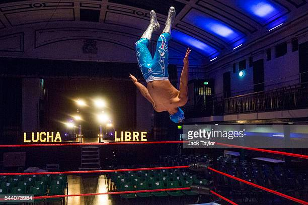 Professional wrestler Magnifico leaps from the ropes of a wrestling ring during a photo call at York Hall in Bethnal Green on July 1 2016 in London...