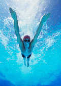 Professional young male athlete swimming in pool