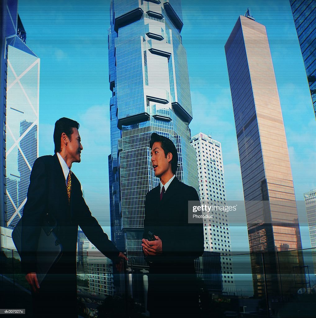 Professionals talking, skyscrapers beyond : Stock Photo