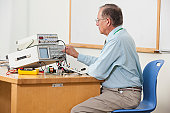 Professor adjusting oscilloscope triggering level in electronics classroom