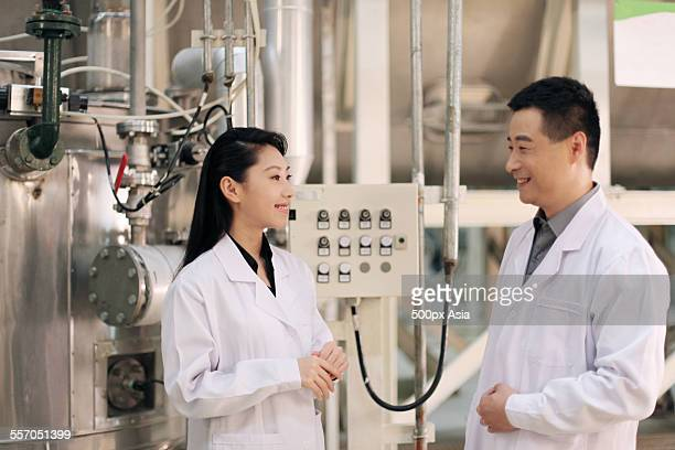 Professor and Student Talking in Factory