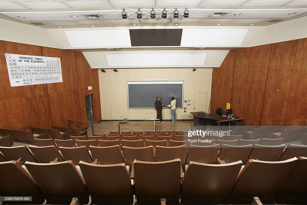 Professor and student working together at chalkboard, elevated view : Stock Photo