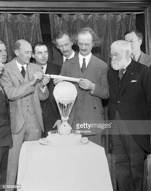 Professor Auguste Piccard noted Belgian aeronaut measures his remarkable birthday cake at the party which was given in honor of his 49th birthday...