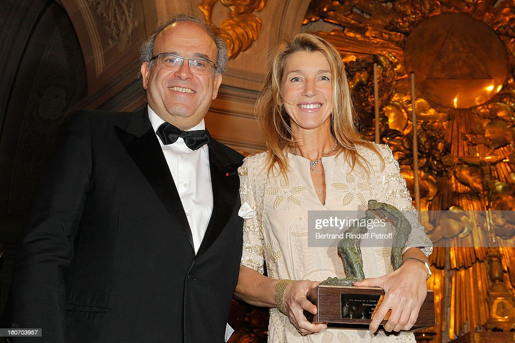 Professor David Khayat (R) and sculptor Helene Jousse, who sculpted the award she holds, pose after Jousse received the Special Prize of the Paris Charter against Cancer during the gala dinner of Khayat's association 'AVEC', at Chateau de Versailles on February 4, 2013 in Versailles, France.