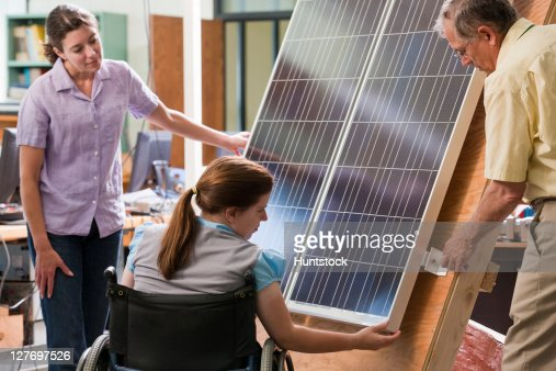 Professor explaining mounting of photovoltaic module to engineering students : Stock Photo