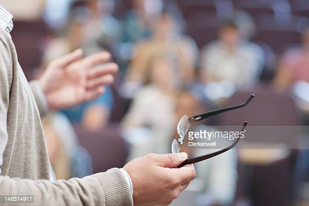 Professor holding eyeglasses and gesturing in lecture hall