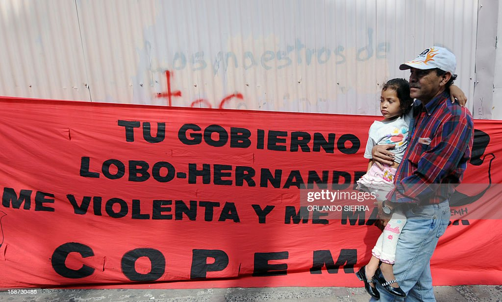 A professor holds her girl during a teachers union protest demanding the pay of salaries and extra month's salary paid at Christmas, in front of the Treasury headquarters in Tegucigalpa on December 26, 2012. AFP PHOTO / Orlando SIERRA