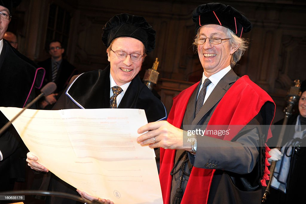 Professor Hugues Duffau of France (L) and KUL's Rector Mark Waer look at a document during a press conference ahead of the honorary degrees ceremony on the occasion of the KU Leuven university's Patron Saint's Day, on February 4, 2013. Duffau is the coordinator of the Neurosurgery unit of the CHU in Montpellier.