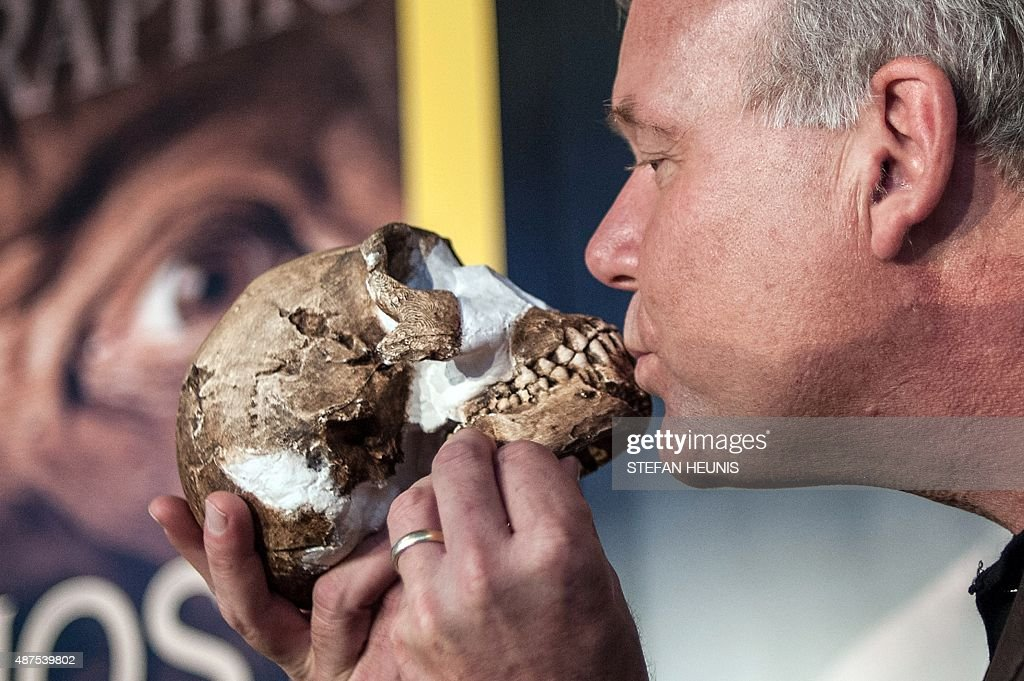 Professor Lee Berger kisses a replica of the skull of a Homo Naledi a newly discovered human ancestor during the unveiling of the discovery on...