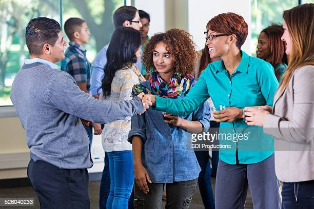 A professor meeting student and parents during orientation