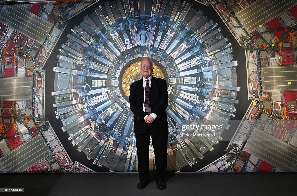 Professor Peter Higgs stands in front of a photograph of the Large Hadron Collider at the Science Museum's 'Collider' exhibition on November 12, 2013 in London, England. At the exhibition, which opens to the public on November 13, 2013 visitors will see a theatre, video and sound art installation and artefacts from the Large Hadron Collider, providing a behind-the-scenes look at the CERN particle physics laboratory in Geneva. It touches on the discovery of the Higgs boson, or God particle, the realisation of scientist Peter Higgs theory.