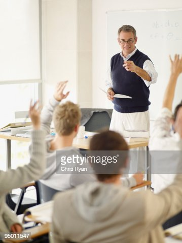 Professor pointing at college students with hands raised in classroom