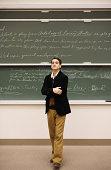 Professor standing in front of chalkboard