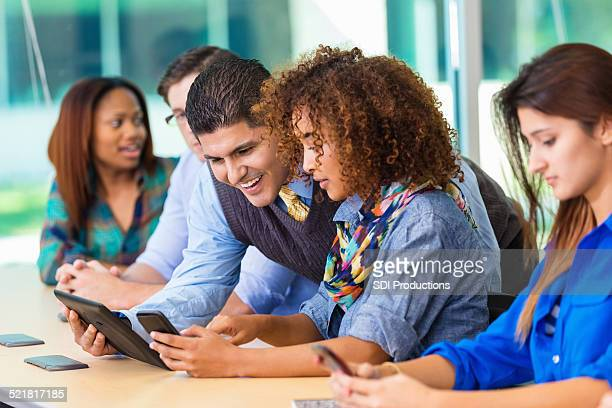 Professor Unterricht vielfältige Gruppe von Studenten, die mit moderner Technologie
