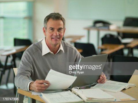 Professor using  laptop with reveiwing paperwork in classroom